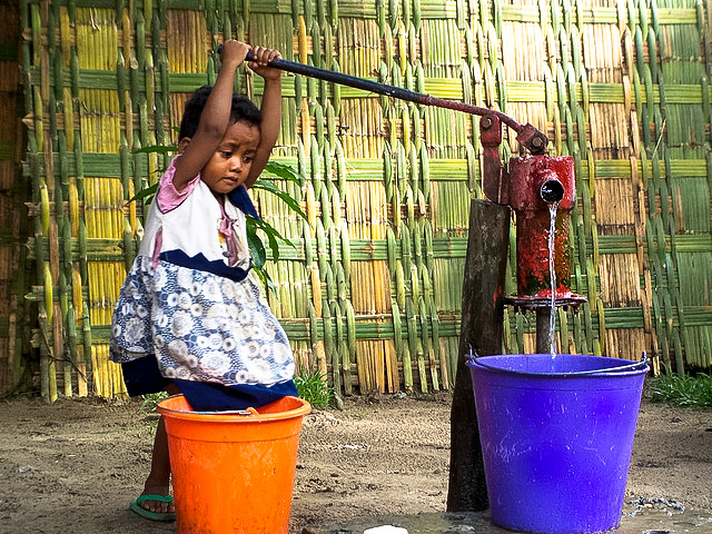 travel the world: child pumping water in madagascar