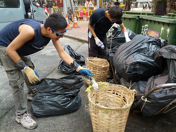 Volunteers collect glass for recycling Why Hong Kong is Drowning in its Own Waste with No Buoy in Sight