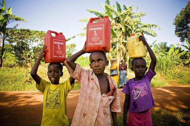 Boys Carry Water Along Road in Ugandan Village