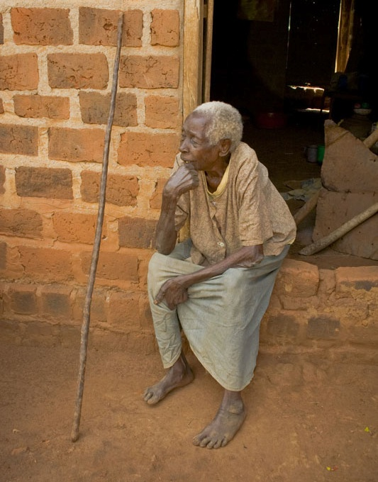 Abigail Nabwire (87) sits outside the room shared with children she cares for, plus an additional family.