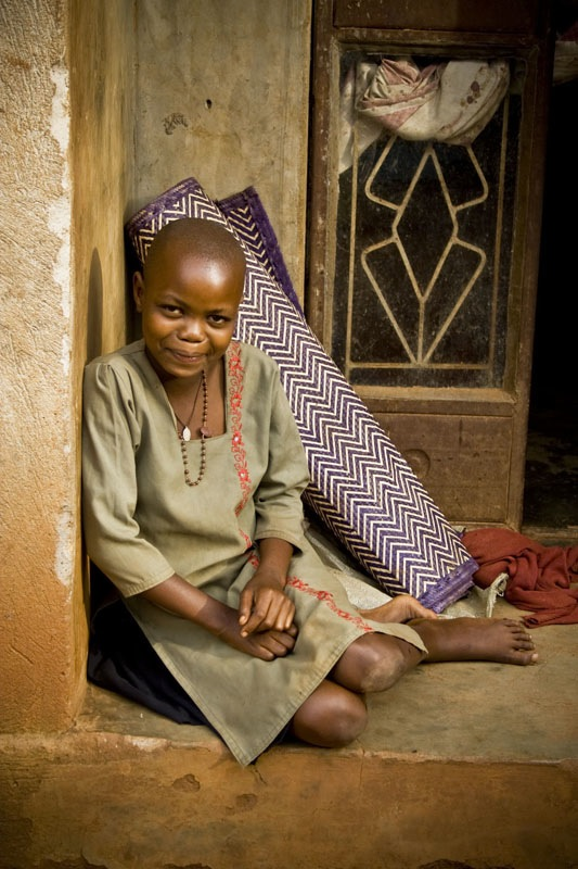 Girl Relaxes on Front Porch in Central Uganda
